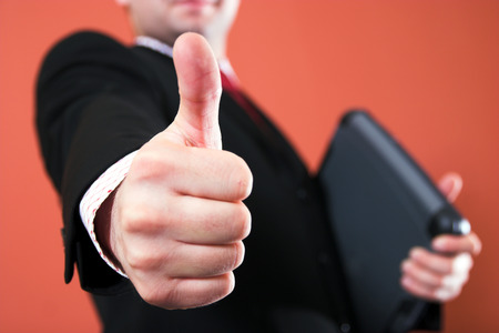 Businessman with laptop, holding thumb up photo
