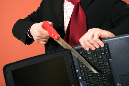 Frustrated businessman sawing the laptop Stock Photo