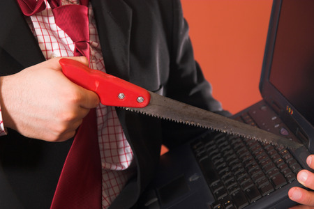 Frustrated businessman threatening laptop with a saw Stock Photo - 1567791