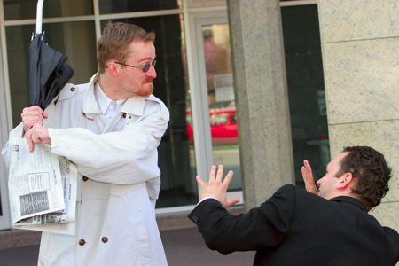 One businessman attacking another with an umbrella Stock Photo - 1567787