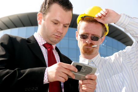 Young businessman showing something on a cell phone(PDA), to a construction worker in front of a corporate building photo