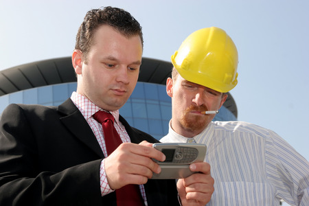 Young businessman showing something on a cell phone(PDA), to a construction worker in front of a corporate building Stock Photo - 1567765