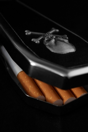 Cigarettes in a coffin cigarette-case with a scull cut Stock Photo