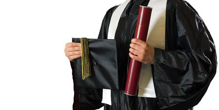 Graduate student holding a diploma and a mortarboard Stock Photo