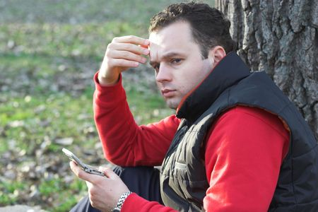 solicitous: Man holding a mobile phone and thinking