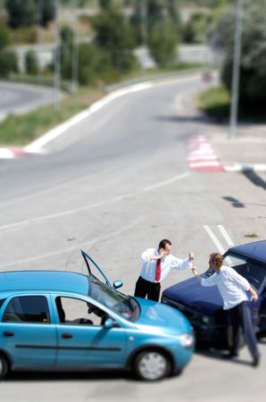 Illusion of miniature traffic accident and two drivers fighting photo