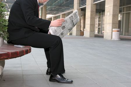 Young businessman reading newspapers