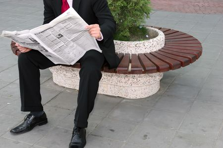 Businessman sitting on the bench and reading newspapers photo