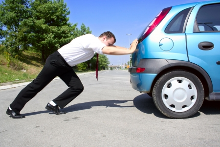 broken car: Hombre en el juego de negocio que empuja un coche quebrado o un coche del gas Foto de archivo