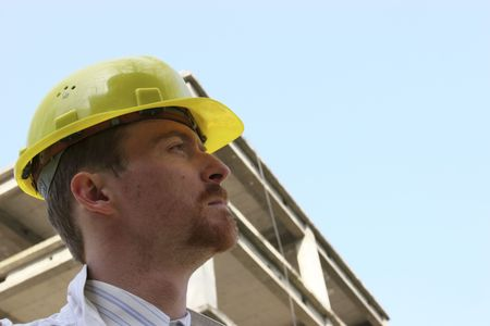 Man with helmet in front of a building construction