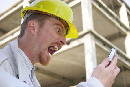 Crazy man with helmet talking on a cell phone in front of a building construction Stock Photo - 1746690