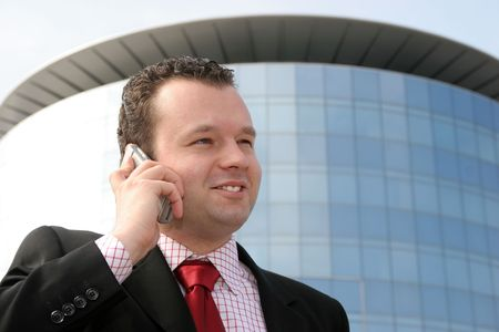 Young businessman smiling and talking on a cell phone in front of a corporate building