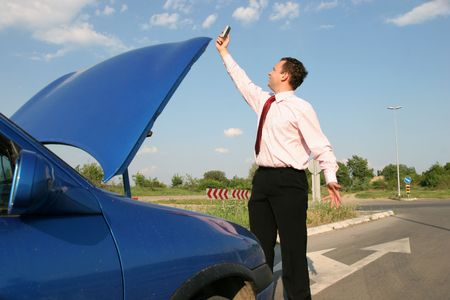 Businessman searching for a mobile network in front of a broken car