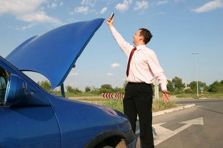 broken car: Empresario busca de redes de telefon�a m�vil frente a un coche roto  Foto de archivo
