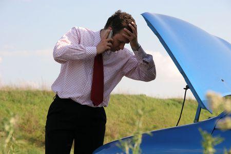 broken car: Hombre de negocios en un tel�fono m�vil delante de un coche quebrado