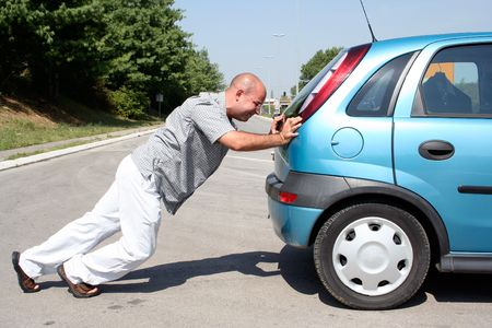 Man pushing a broken car or a car out of gas photo