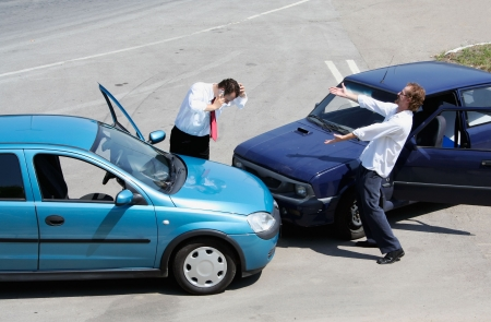 Traffic accident - one driver on the mobile phone, second expressing anger Stock Photo