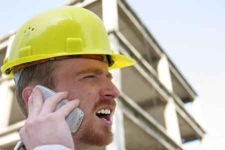 Man with helmet talking on a cell phone in front of a building construction