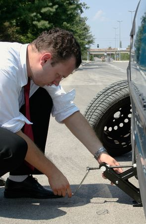 Businessman changing a flat tire on the road