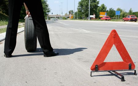 man wth a flat tire and a triangle on the road Stock Photo - 1950801