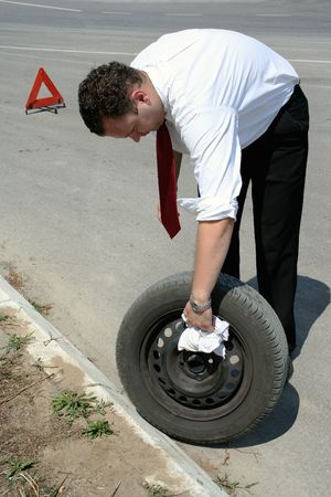 jack tar: Businessman changing a flat tire on the road