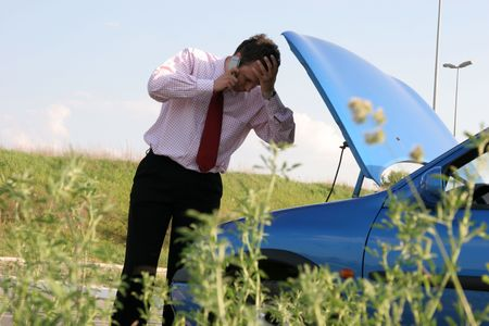 Businessman on a mobile phone in front of a broken car