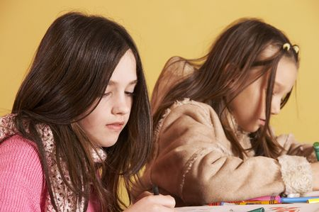 Two young schoolgirls drawing together