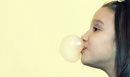 Young girl making a bubble from chewing gum Stock Photo
