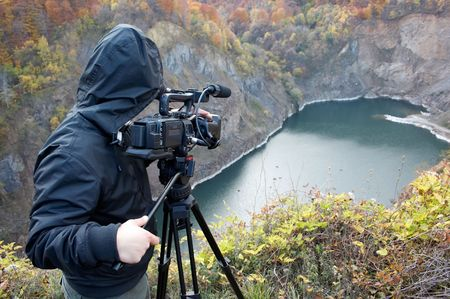 Nature photographer with digital camcorder on top of the mountain lake