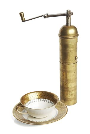 Elegant coffee cup and old brass manual mill photo