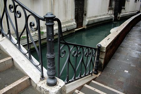 balustrade: A small bridge with wrought iron fence over the canal in Venice Stock Photo