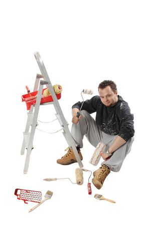 Painter sitting and holding a paint rollers