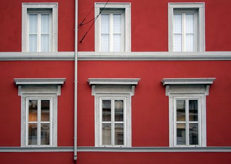 Detail of a red facade building with six windows