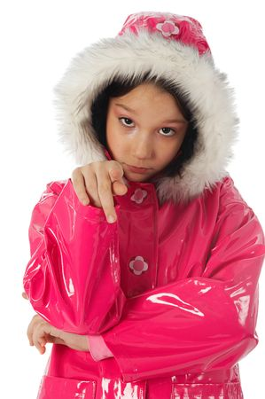Young girl in a pink raincoat with woolly hood, pionting a finger to the camera photo