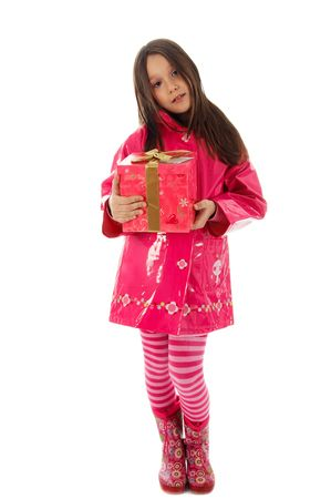 Young girl in a pink raincoat holding a present Stock Photo