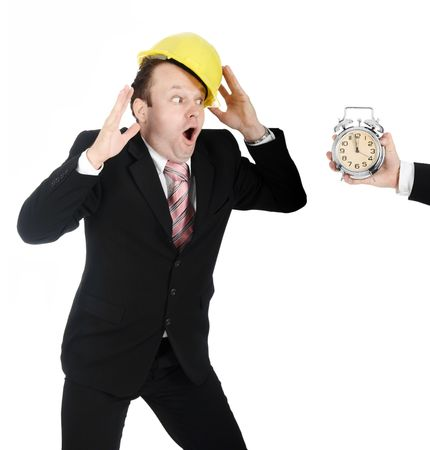 Man in a business suit and a hardhat, making a funny reaction on a clock