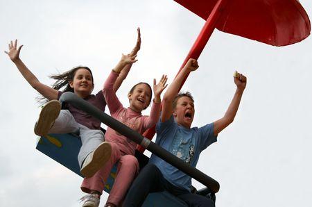 Three kids enjoying a ride on a carousel Stock Photo