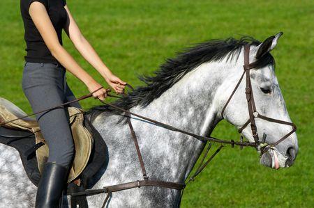 Girl jockey riding a white-gray horse