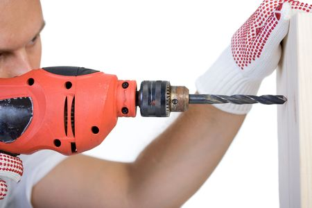 Man holding a drill on a peace of wood plank photo