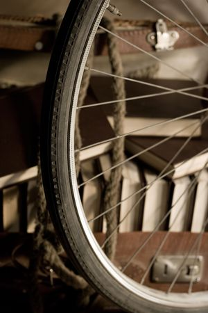 travelling salesman: Bicycle wheel and Old torn suitcase full of books with rope