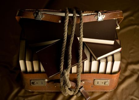 travelling salesman: Old torn suitcase full of books and a rope holding it together