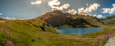 cloud capped: Panorama of glacial lake in Alps Stock Photo