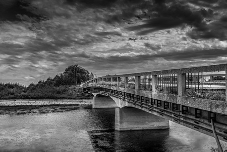 Panorama of old abandoned bridge across river in black and white Stock Photo