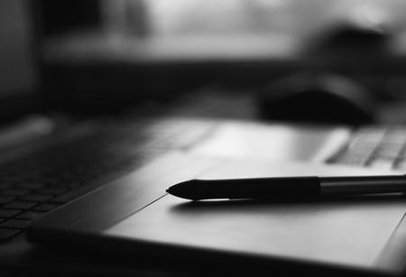 close-up van een grafische tablet met een pen in donkere kleuren Stockfoto