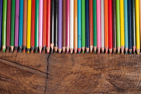 colored pencils on wooden table, copy space