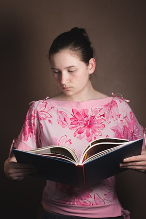 hard cover: young beautiful girl reading a book in hard cover