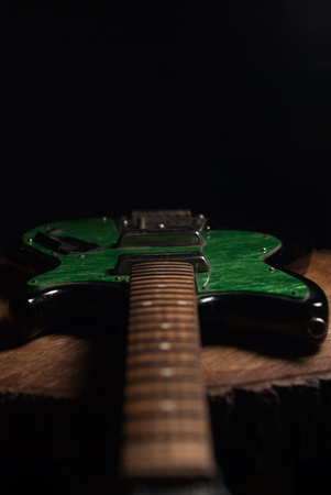 dim light: electric guitar with green accents in the dim light, blur