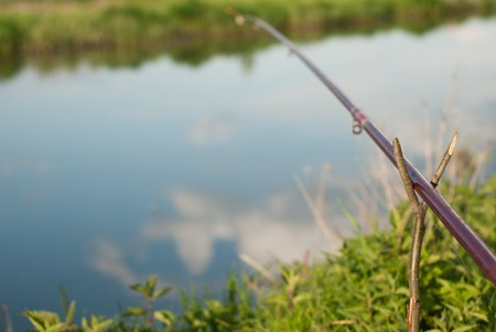jigging: Fishing: fishing rod on the Bank of the river, the sky reflected in the water of the river Stock Photo