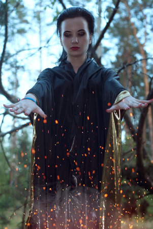 mage: a young witch in the woods, a woman in a dark dress on a background of old branches, the mage uses spells with sparks Stock Photo