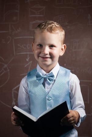 graduation suit: Little schoolboy with blond hair in a nice suit, an emotional student with book in hand, a boy posing on the background of the Board